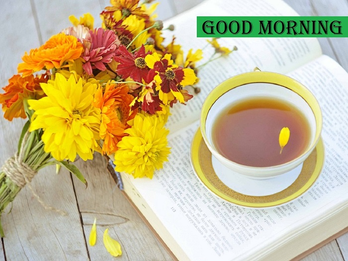 Good Morning with hot cup of tea and yellow flowers